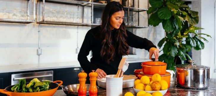 A woman standing in front of a bowl of food