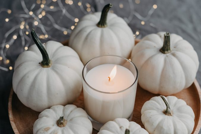 White pumpkins surrounding candle
