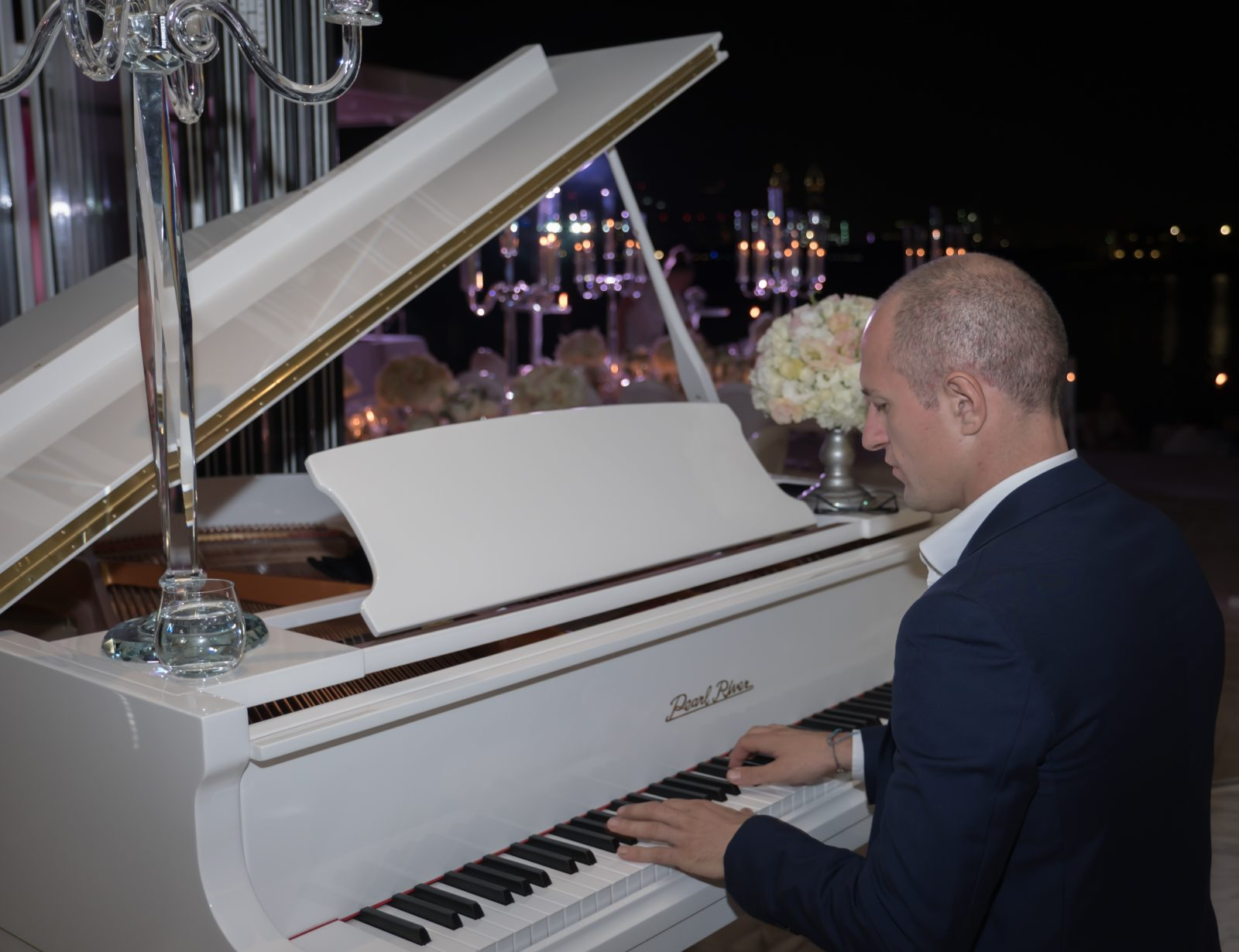Man playing a baby grand white piano