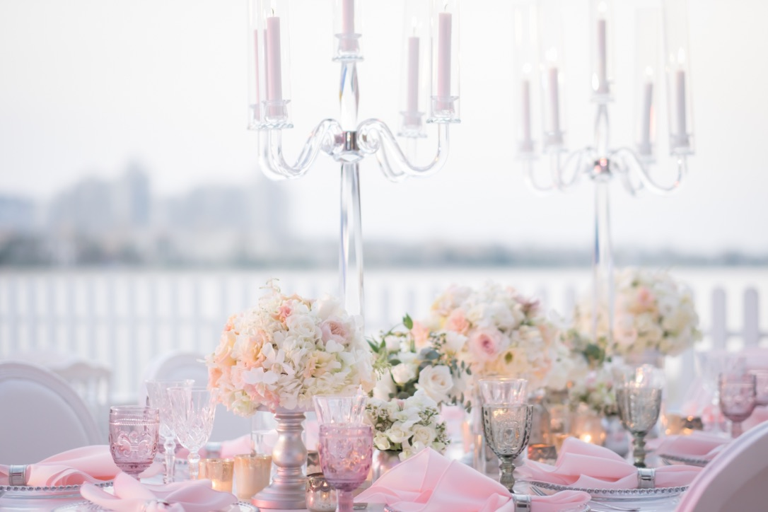 Beautifully laid dining table with candelabras and pink and white flowers