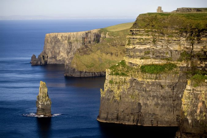 A stone bridge over a body of water with Cliffs of Moher in the background