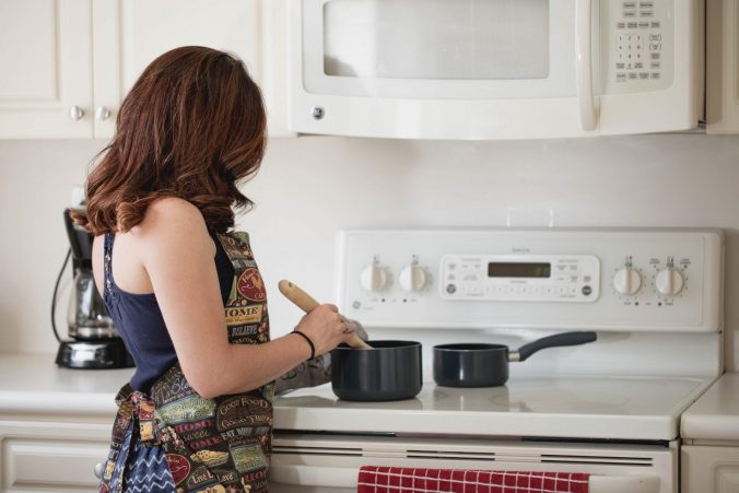 A woman standing in front of a stove top oven